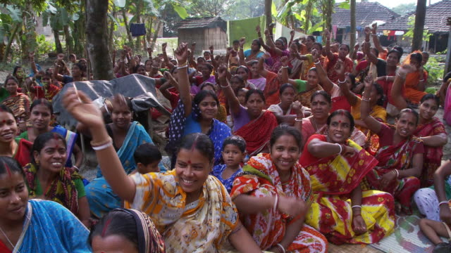 Women chanting, walking and raising arms at  women meeting