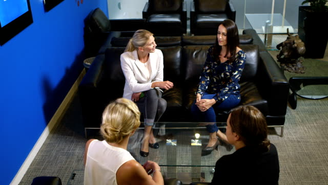 Women chatting in a corporate office setting