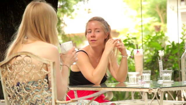 Women Chatting over Coffee. Cafe Scene. Outdoors.
