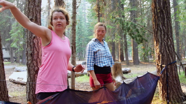 Women Chatting While Setting Up Camping Hammock