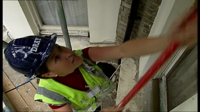Women construction workers treating old sash windows of London townhouse Women construction workers doing work on windows including scraping paint...