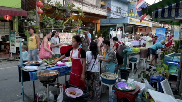 Women cook in a food stall at night market