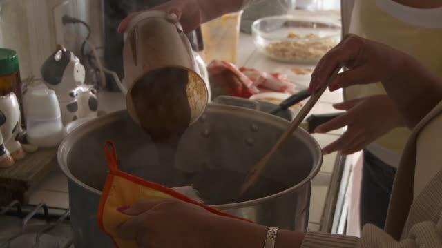 CU Women cooking and stirring mole sauce in pot / Cuernavaca, Morelos, Mexico