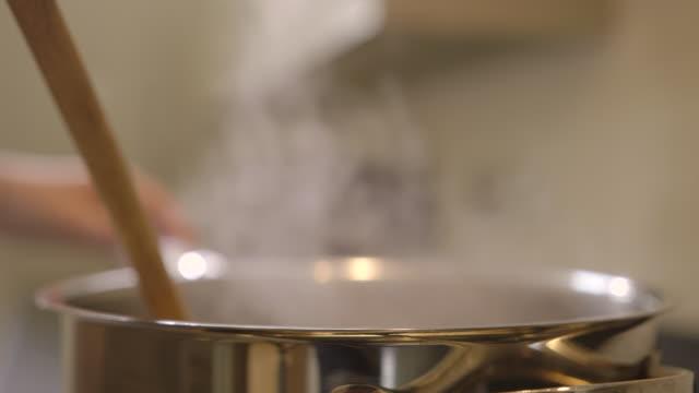 C/U Women cooking in modern kitchen