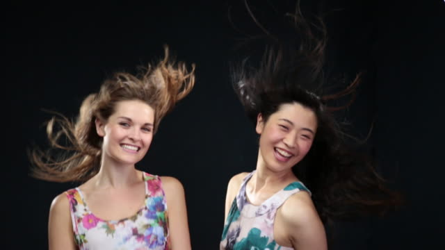 MS SLO MO Women dancing and laughing and wind blowing hair / London, Greater London, United Kingdom