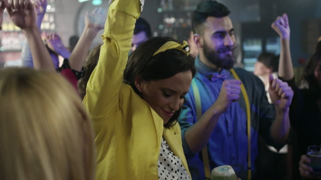 Women dancing with her friends in cocktail bar