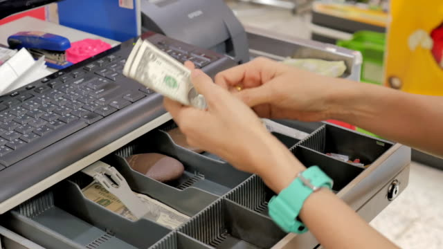 Women dispensing change and counting from a register cash drawer