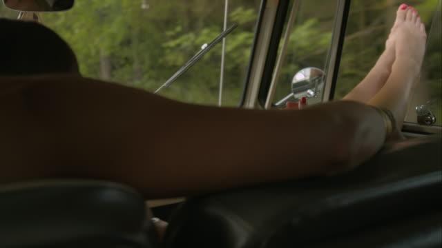 Women driving retro van along street