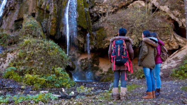 Women enjoying nature near waterfall