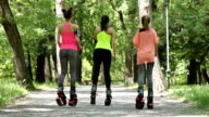 Women exercising and jumping on the park alley. Rear shot view.