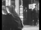 Women exit polling place passing line of people waiting to enter / nuns exit polling place walk together / man and woman walk down steps after...