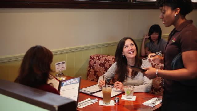 MS PAN Women giving food order to waitress  / Truxton's, California, USA