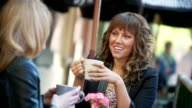 Le donne hanno un bicchiere di latte al caffè all'aperto.
