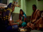 Women have bangles placed on wrist as part of religious ritual India