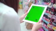 Women Holding Blank Tablet PC With Green in supermarket,Close-up