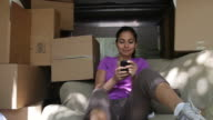 MS PAN Women in back of moving truck using smart phone / Newark, New Jersey, United States