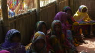 Women in colourful saris from a small village in Northern Bangladesh gather in the thatch meeting room for healthcare advice from an NGO