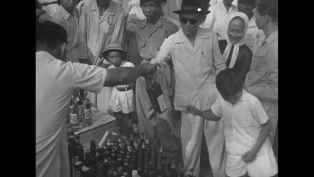 Women in flower market / man in sunglasses handed bottle of liquor / bustling street / wooden wagon pulled by water buffalo / street with palm trees...