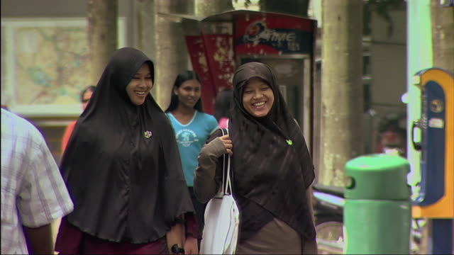 MS Women in headscarf crossing street / Malaysia
