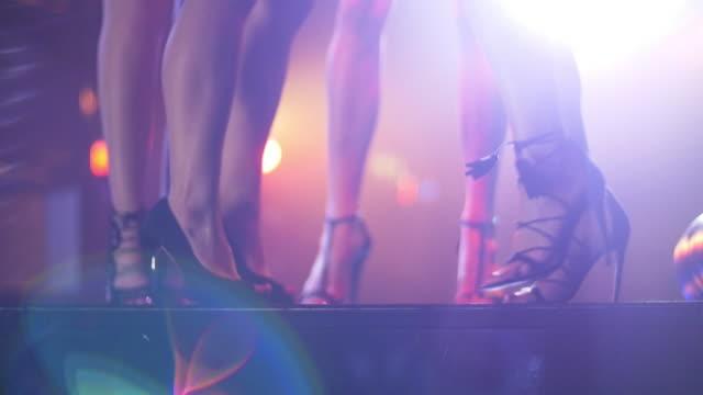 SLO MO Women in high heels dancing on nightclub table