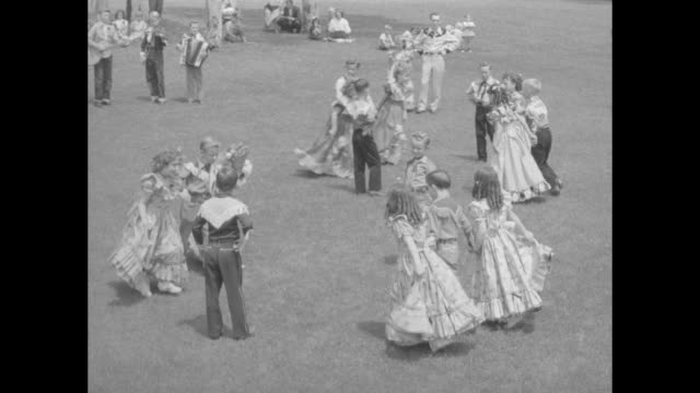 Women in matching dresses and men in bolo ties stand outdoors twobytwo in a square VO music begins and VO square dance caller begins to call the...