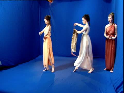 Women in Roman dresses dance in front of a blue screen.
