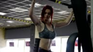 Women in Sport. Redhead fitness woman pulls up on the simulator