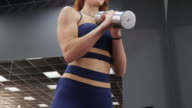 Women in Sport. Redhead fitness woman training with dumbbells