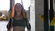 Women in Sport. Redhead fitness woman training with trx fitness straps