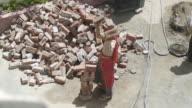 Women Laborer carrying bricks on head