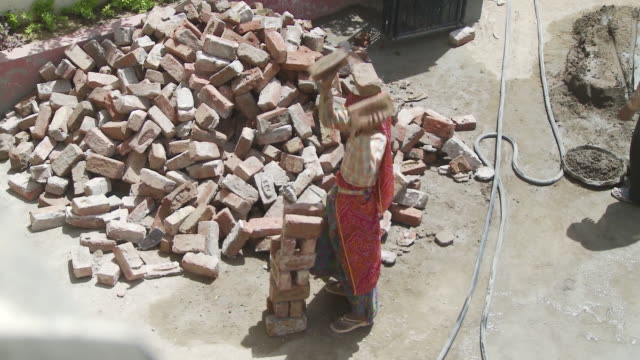 Women Laborer carrying bricks on head