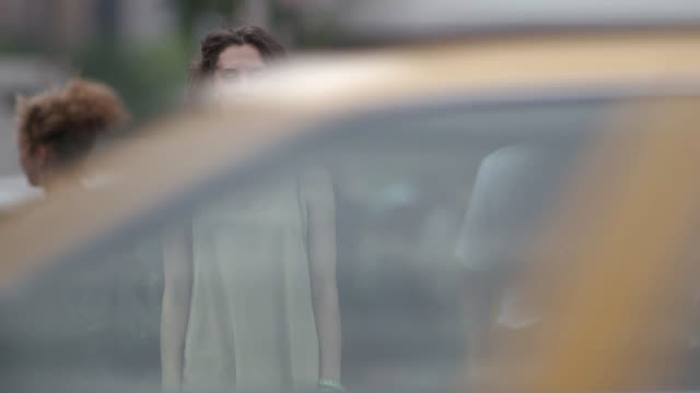 A women looks at camera while cabs drive in front.  She is standing at a street corner in NYC.