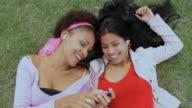 CU Women lying on grass, listening music and sharing headphones / Havana, Cuba