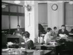 B/W 1927 women + men working at desks in office / women typing / industrial