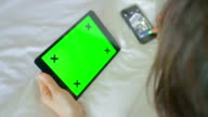 Women on bed using a Digital Tablet at home,Green screen