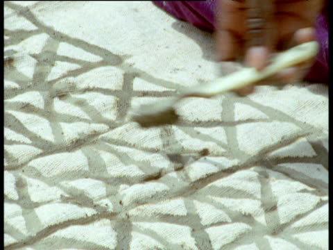 Women paint designs on cloth using toothbrush, Djenne