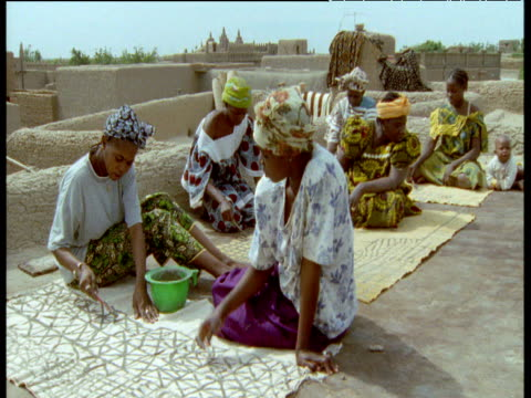 Women paint designs on cloth using toothbrushes, Djenne
