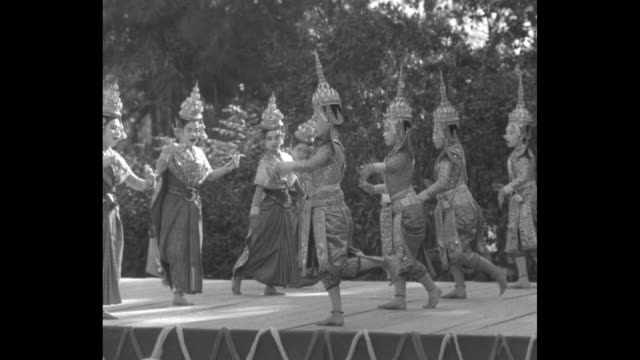 WS women perform Kandyan dance on round stage dressed in traditional ethnic clothing / WS seated white tourists watching man plays xylophone in...