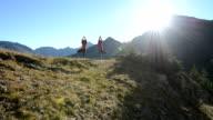 Women perform yoga exercises in mountain meadow
