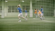 Women playing friendly soccer match in indoor field