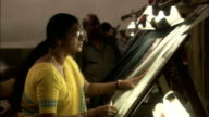 Women process fabric in busy textiles factory Available in HD.