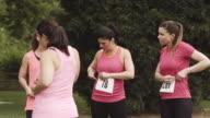 Women putting race bibs on before breast cancer run