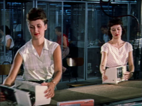 1959 women putting together clock radios on assembly line