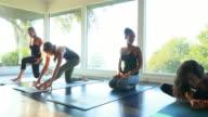 MS PAN Women resting between poses in yoga class in studio