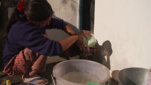 Women rinses little girls hair with water