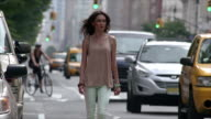 A women rounds the corner and steps into the bike lane and walks down the street
