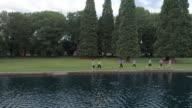 Women running next to a pond