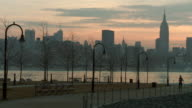 A women running on a park walkway with the Manhattan Skyline behind.