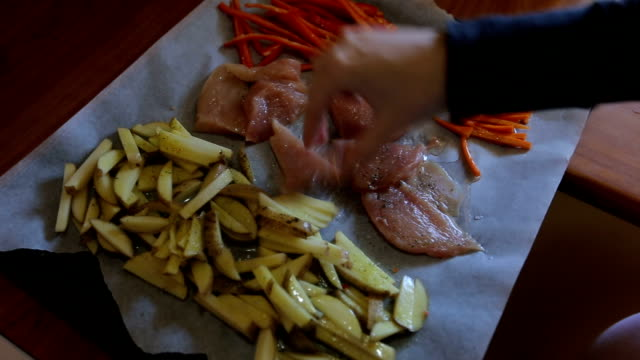 Women seasoning vegetables an chicken meat
