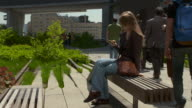 Women sending a text on her phone while sitting on a park bench on the Highline park in New York.